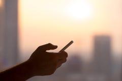 有智能手机的男性手在日落 免版税库存照片