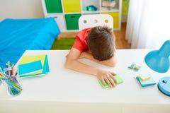 有智能手机的疲乏或哀伤的学生男孩在家 库存图片