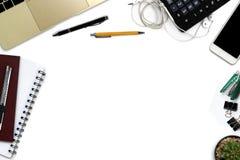 有智能手机的白色办公桌有黑屏幕的,笔,膝上型计算机 免版税库存照片