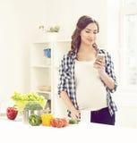 有智能手机的美丽的孕妇在厨房里 母性, 库存图片