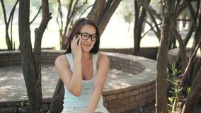 有智能手机的美丽的快乐的女孩在公园在长凳坐一个晴天 库存照片