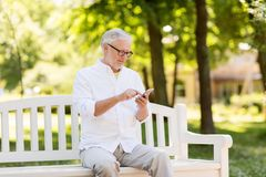 有智能手机的老人在夏天公园 免版税库存照片