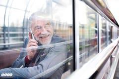 有智能手机的老人在打电话的玻璃段落 免版税库存照片