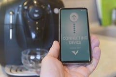 有智能手机的连接的咖啡机 免版税库存照片