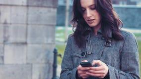 有智能手机的年轻女商人在办公室外 股票录像