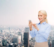 有智能手机的年轻微笑的女实业家 免版税图库摄影