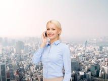 有智能手机的年轻微笑的女实业家 库存图片