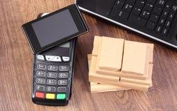 有智能手机的付款终端有NFC技术的、膝上型计算机和箱子在板台,无钱支付运输和产品 免版税库存照片