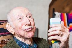 有智能手机的更老的绅士 库存照片