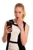 有智能手机communi的美丽的年轻白种人女商人 免版税库存图片