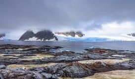 有暗藏的山和蓝色冰川的岩石海岸线全景 免版税库存照片