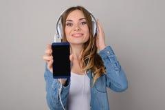 有暴牙的微笑的俏丽的妇女听到音乐的通过耳机 库存图片