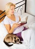 有暹罗猫和书的成熟妇女 库存照片