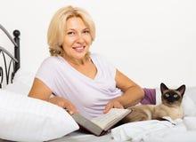 有暹罗猫和书的成熟妇女 免版税图库摄影