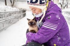 有暹罗猫的妇女在冬天 免版税库存图片