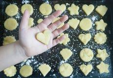 有曲奇饼心脏的手在TRAY_ 免版税库存图片