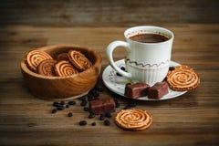有曲奇饼,糖果,巧克力豌豆,鸦片; 瓷茶碟和盖帽有Coffe的,鲜美甜食物在木背景,被定调子 库存图片
