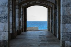 有曲拱岩石海岸&透亮海的建筑 免版税库存图片