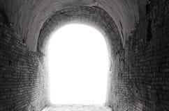 有曲拱开头光的老黑暗的隧道走廊在t结束时 免版税库存照片