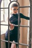 有曲拱窗扇的确信的美丽的妇女 库存照片