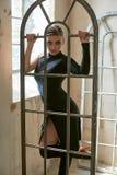 有曲拱窗扇的确信的美丽的妇女 免版税库存图片