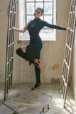 有曲拱窗扇的确信的美丽的妇女 图库摄影