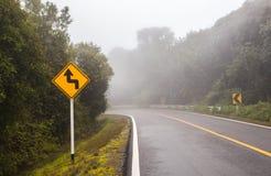 有曲线标志的有风森林公路在土井Intha的一有雾的天 免版税图库摄影