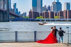 有曼哈顿下城地平线的,与一件巨大的红色礼服的时尚会议布鲁克林大桥在纽约 图库摄影