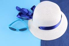 有最高荣誉的帽子在与蓝色太阳镜的一块蓝色毛巾在蓝色背景 海滩辅助部件 库存图片