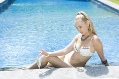 有有一头长的金发的,在比基尼泳装游泳衣的一个微小的图美丽的妇女关于与明亮的大海的水池在回归线 免版税库存图片