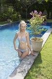 有有一头长的金发的,在比基尼泳装游泳衣的一个微小的图美丽的妇女在与明亮的大海的水池在热带 库存图片