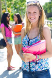 有有些朋友的俏丽的学生女孩在学校以后 免版税库存图片