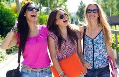 有有些朋友的俏丽的学生女孩在学校以后 库存图片