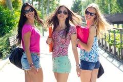 有有些朋友的俏丽的学生女孩在学校以后 免版税库存照片