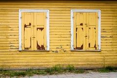 有有些窗口的黄色木墙壁 免版税库存照片
