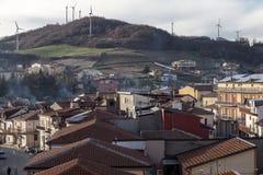 有有些风力发电机的一个小的镇在小山的上面 库存图片