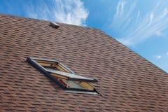有有双重斜坡屋顶的房屋的窗口和沥青木瓦的屋顶 打开在屋顶木瓦的天窗建设中 免版税库存图片