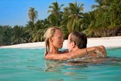 有有吸引力的夫妇在热带海滩的风扇 免版税库存图片