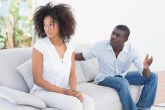 有有吸引力的夫妇在长沙发的一个论据 免版税图库摄影