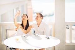 有有吸引力的夫妇第一个日期 与朋友的咖啡 做与智能手机的微笑的愉快的人民一selfie 免版税库存照片