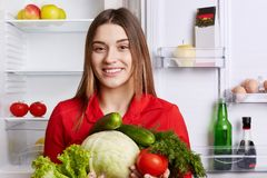有有吸引力的神色的逗人喜爱的快乐的女性保持节食,去做菜沙拉,保留圆白菜,黄瓜,蕃茄, lettuc 免版税库存图片