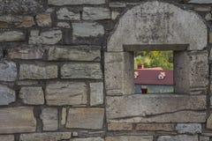 有有塑料玻璃用一个棕色饮料的漏洞的一个老石墙 免版税库存照片