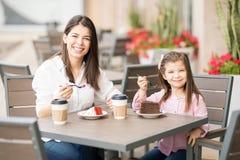 有有她的小的女儿的妇女蛋糕 免版税库存照片