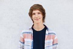 有有时髦的发型的时髦的十几岁的男孩黑眼睛、纯净的皮肤和笑涡在穿衬衣的面颊站立反对白色c 免版税库存照片