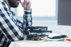 有有显示卡和金钱在他的书桌上的胡子的一个人 免版税库存图片