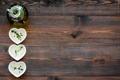有有机油的瓶与在木背景顶视图大模型的草本成份 免版税图库摄影