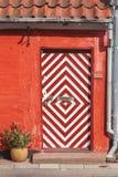 有有条纹的门的红色房子 图库摄影