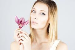 有有桃红色花的秀丽金发碧眼的女人在手中 清楚和新鲜的皮肤 秀丽表面 库存图片