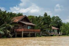 有有棕榈农场的河沿泰国房子 免版税库存图片