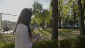 有有步行在公园和使用智能手机的长的头发的年轻美丽的女商人在慢动作- 股票录像